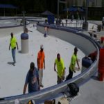 Construction crew rolling on plaster for pool