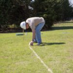 Placing chalk lines to mark the outside area of the hole to be dug.