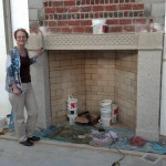 Sue Drew next to a large fireplace